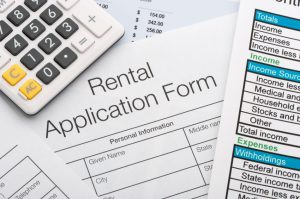 Close up of rental application with calculator and pen